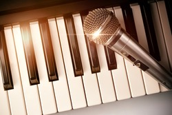 Piano and microphone with golden sparkles. Horizontal Composition.Top view