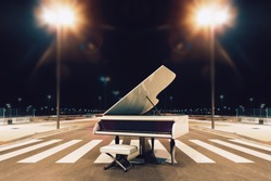 Piano and song concept..White piano in city street at night.Urban music and night entertainment.
