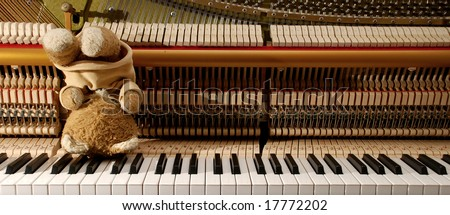 Piano keyboard and teddy bear in upside down position - frustrated in waiting for inspiration concept