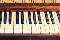 Piano keyboard background with selective focus. Warm color toned image