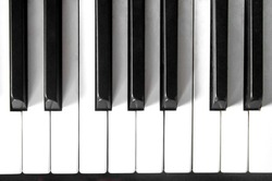 Piano keyboard with black and white on top view with light shadow.