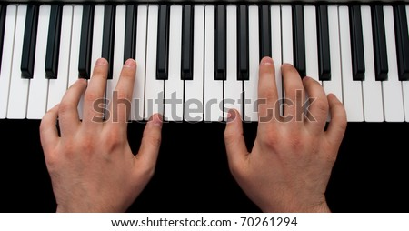 piano keyboard with hands on black background