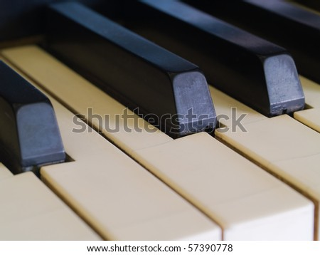 Piano keys of a very well loved and often played piano showing some wear and cracking.