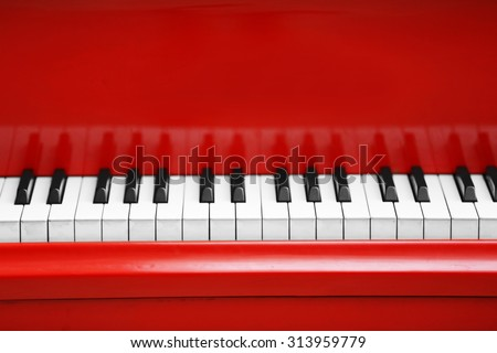 Piano keys of red piano close up