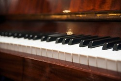 Piano keys on wooden brown musical instrument. Horizontal. View from the side