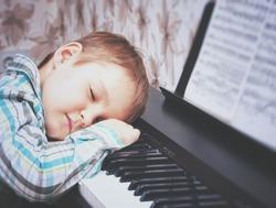 Piano keys. The boy is sleeping on the piano keys. Hands of the boy on the piano keys. The boy is tired and asleep after piano lessons.