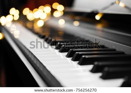 piano keys with beautiful yellow lights bokeh in background, piano keys with  Christmas lights, concert, backstage