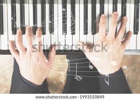 Piano learning chords at home, hands playing keyboard with an online music lesson.