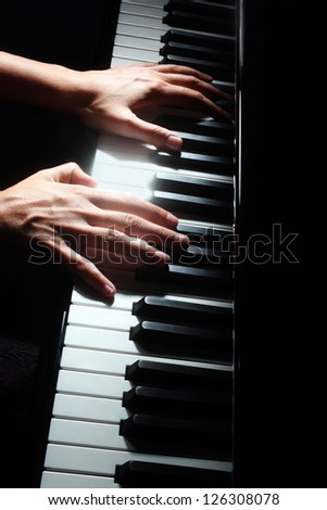 Piano music pianist hands playing. Musical instrument grand piano details with performer hand on black background