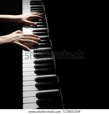 Piano player. Pianist playing musical instrument close up. Grand piano with hands closeup #573835504