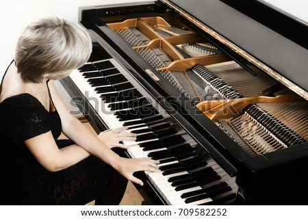 Piano player. Pianist woman playing grand piano Open musical instrument