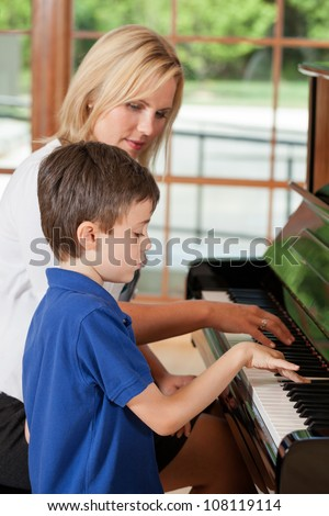 Piano teacher giving lessons to a young boy