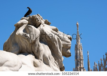 Piazza del Duomo in Milan, Italy. Detail of lion statue and Duomo di Milano (Milan Cathedral) in the background