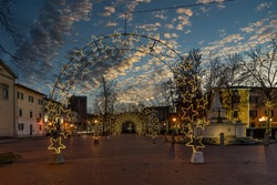 Piazza Vittorio Emanuele II square in the center of Bientina, Pisa, Tuscany, Italy, fully decked out with Christmas lights for the seasonal holidays, at sunset