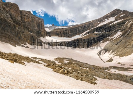 Pic du Taillon in the crown of Cirque de Gavarnie in French Pyrenees. The slope in the foreground is almost completely covered with snow, despite the fact that the photo was taken in July.