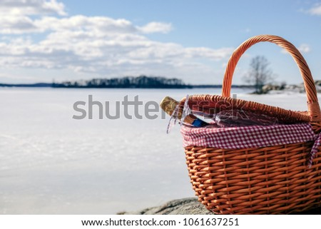 Pic nic basket with champagne glass and bottle on a cliff. Sunny cold day with a frozen lake in the background.
