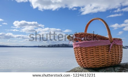 Pic nic basket with champagne glass and bottle on a cliff. Sunny cold day with a frozen lake in the background and a beautiful blue sky with white fluffy clouds.