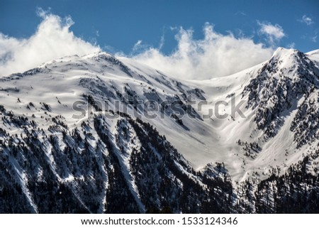 pic of a mountain with snow on a sunny day and blue sky