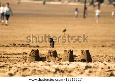 pic of sand castle on the beach  made by children having fun by the sea, during an holiday with the parents in summer or spring. the sunlight is gold from sunset and the background is blurred