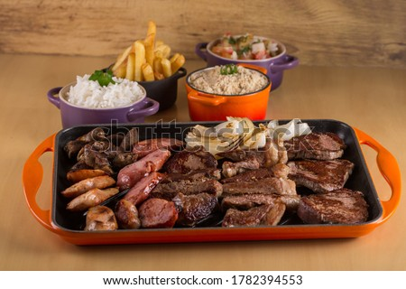 Picanha, a traditional cut of Brazilian meat, served with grilled onion and sausage on a hot iron plate. Brazilian barbecue served on a hot iron plate accompanied by rice, farofa and french fries