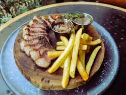 Picanha steak with frenchfries,on black iron table.