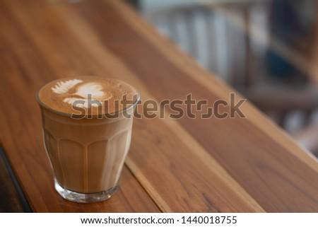 Piccolo Latte art in small glass on wooden desk. #1440018755