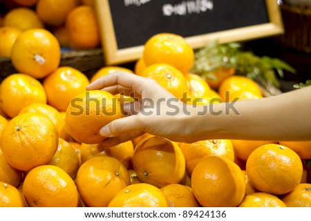 pick orange, female hand pick up Sunkist orange in market.