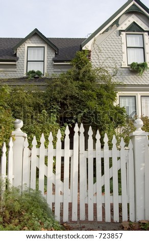 Picket fence entry gate leads to an overgrown front yard of an old house.