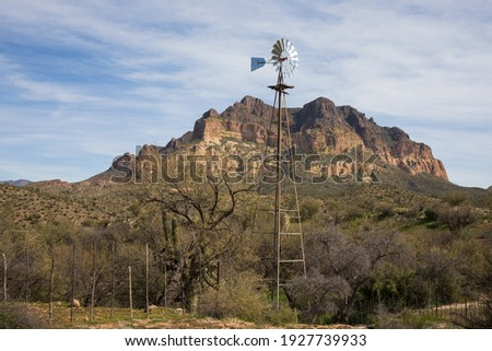 Picket Post Mountain in Arizona with a water tank's windmill and desert wash in the foreground.  Also known for the site of Apache Leap and the natural obsidian deposits known as Apache Tears.