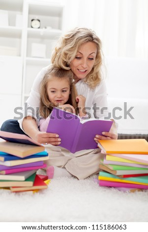 Picking a story to read - little girl and her mother at home
