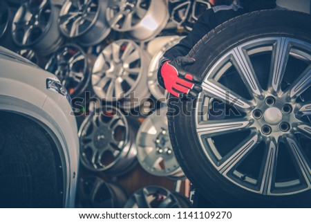 Picking New Alloy Wheels. Car Service Mechanic with Large Sport Utility Vehicle Wheel. #1141109270