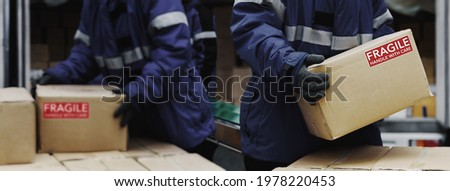 Picking up package fragile boxes in loading area of cold storage warehouse prepare to transfer storage in the freezing room, Warehouse Storage System Support Logistics Business in Banner size.