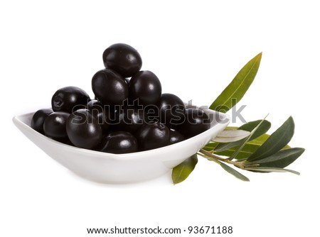 Pickle black olives in a bowl and olive tree branch on a white background