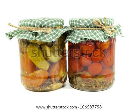 pickled cucumbers and tomatoes canned in glass jar on  a white background
