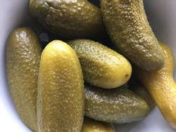 pickled cucumbers close-up lie in a bowl with black edges