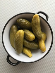 pickled cucumbers close-up lie in a bowl with black edges on a gray striped background