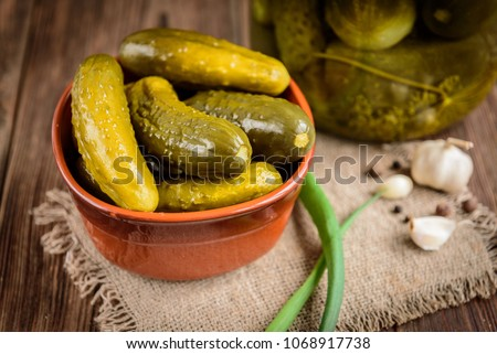 Pickled cucumbers in bowl on wooden rustic table with garlic and jar of pickles. Сток-фото ©