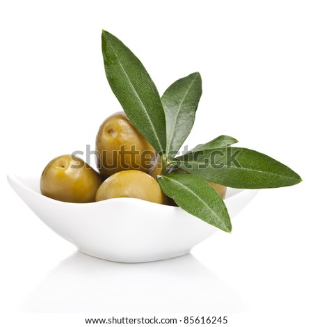 pickled green olives in a bowl and olive tree branch on a white background