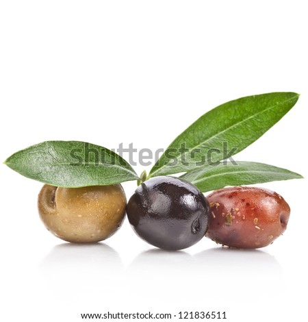 pickled olives with spices and olive tree leaves close up isolated on white background