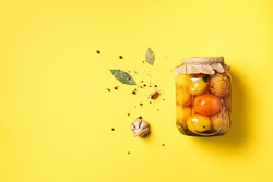 Pickled tomatoes in jar on yellow background. Top view. Flat lay. Copy space. Canned and preserved vegetables. Ingredients for vegetables preserving. Healthy fermented food concept