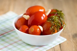 Pickled tomatoes with dill and garlic with white bowl