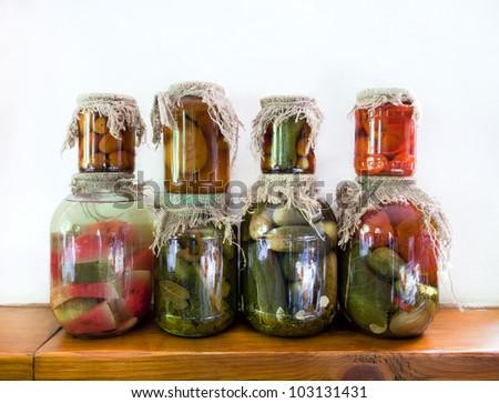 Pickled vegetables in glass jars on a wooden shelf