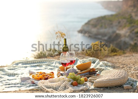 picknick outdoors with fruits and wine by sea in naure Stockfoto ©