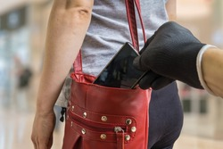 Pickpocket thief is stealing smartphone from red handbag.