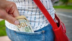 Pickpocketing, offender stealing cash from back pocket in the street. Stealing money, street robbery. Male hand steal money from female pocket, pickpocket hand with dollars cash.