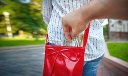 Pickpocketing, thief stealing cash from womans red handbag in the street. Stealing money, street robbery. Male hand steal money from female handbag, pickpocket hand with dollars cash.