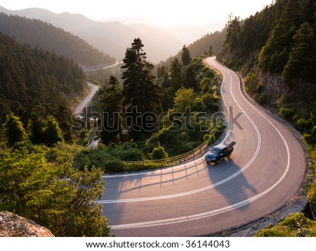 Continental Greece pickup crosses mountain road winding in twilight