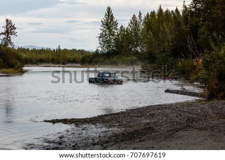 Pickup truck abandoned in high waters of Alaska river #707697619