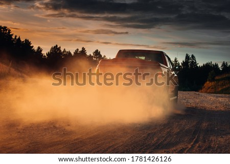 Pickup truck car in motion at country road with clouds of dust