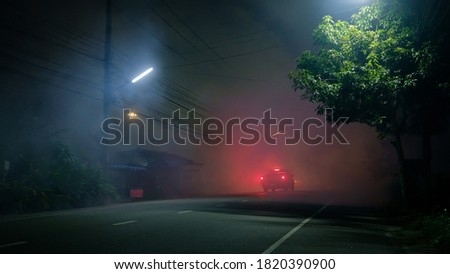 Pickup truck drive into fog on empty road with red taillight in silent town Stockfoto ©